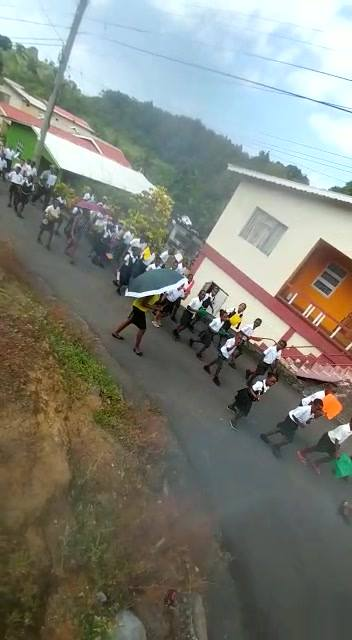 The headteacher, teachers and students marching through the village of Diamond to commence their Literacy Week activitie...